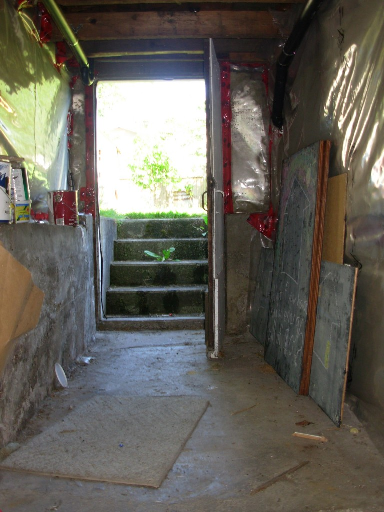 There is a step up to this passage to the basement door. You can see our best attempts to seal and insulate. The concrete foundation wall on the left is not supporting the wall above it.