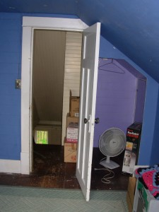 The south upstairs bedroom, looking north down the stairs. Notice the awkward closet and the fan.
